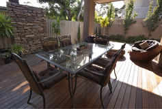 Patio. Modern patio with outdoor dining table and chairs.  Polished timber decking Stock Photography