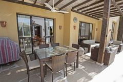 Patio area with sofa and dining table at a luxury tropical holiday villa resort. Luxury villa show home in tropical summer holiday resort with patio area showing stock photo