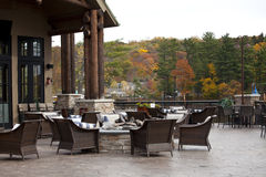 Patio. Autumn landscape with patio and colorful autumn trees. outdoor furniture with stone fireplace stock photos