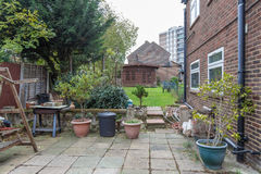 Patio, back garden with a wooden cabin at the back. Stock Photo