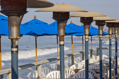 Patio cafe on the pier. Space heaters and umbrellas at an outdoor patio cafe on the San Clemente Pier in California Stock Photos