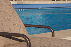 Patio chair next to an aqua blue pool Royalty Free Stock Photography