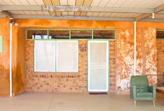 Underground house patio vintage, Coober Pedy, Australia. Patio with a vintage chair from the sixties and the facade of an underground house  in opal mining town Royalty Free Stock Photography