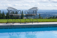 Patio chairs beside a pool. Two wrought iron patio chairs sit beside a swimming pool with a lawn and panoramic view Royalty Free Stock Images