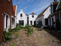 Patio con las casas tradicionales en la isla Texel Imágenes de archivo libres de regalías