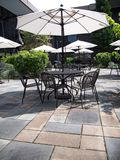 Patio courtyard with table, chairs and white umbrellas Royalty Free Stock Photos