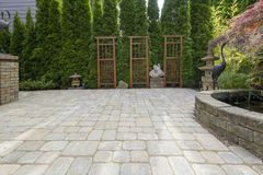Patio de la pavimentadora del patio trasero con la charca en jardín Imagen de archivo libre de regalías