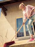 Patio de nettoyage de femme utilisant le balai de brosse images libres de droits