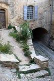 Patio de piedra de tres niveles con un arco y una ventana vieja foto de archivo