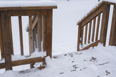 Patio deck entrance during winter with snow. Snow covered golden brown patio deck entrance with steps, leading to open snow field stock photo