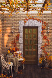 Patio door and brick wall. Entwined yellow autumn leaves Stock Image