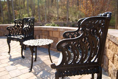 Patio furniture. A couple of Cast-iron chairs on a patio stock photography