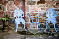 Patio furniture against stone wall Royalty Free Stock Image