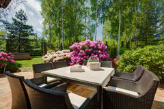 Patio furniture in beautiful garden Royalty Free Stock Photography
