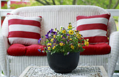 Patio Furniture and Colorful Pansies. White Patio Furniture and Colorful Pansies in a Black Metal Bucket Royalty Free Stock Image