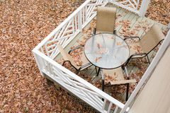Patio table and chairs on a back deck covered in fall leaves. Patio furniture covered with fall leaves on a back deck. The photo is taken from above stock photography