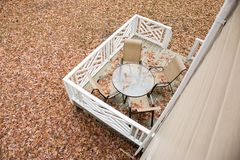 Patio table and chairs on a back deck covered in fall leaves. Patio furniture covered with fall leaves on a back deck. The photo is taken from above stock photos