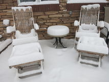 Patio Furniture Covered in Snow. Patio furniture (wooden) is covered in snow in winter Stock Images