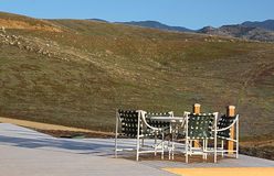 Patio Furniture On A Deck Viewing Fields. A patio furniture set sits on a deck on a sunny day with a view of grassy fields and mountains stock image