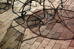 Patio furniture shadow abstsract. Shadows cast on a brick patio by metal outdoor furniture Royalty Free Stock Images