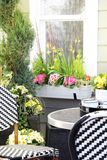 Patio furniture surrounded by spring flowers. Royalty Free Stock Image