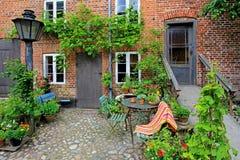 Patio hermoso de la casa vieja con las flores, ciudad real Ribe, Dinamarca imagenes de archivo