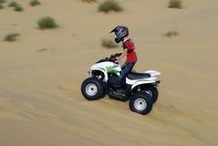 Patio joven del muchacho biking en las dunas Imágenes de archivo libres de regalías