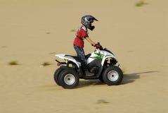Patio joven del muchacho biking en las dunas Fotos de archivo libres de regalías