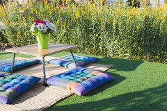 Patio outdoor deck with colorful cushion and flower decoration. On table, exterior of home with yellow flower field stock photo