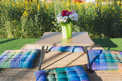 Patio outdoor deck with colorful cushion and flower decoration. On table, exterior of home with yellow flower field royalty free stock image
