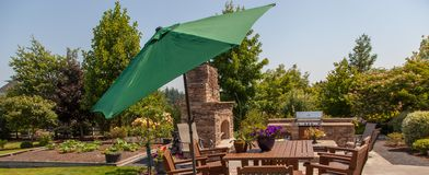 Patio outdoor kitchen and garden with green umbrella. A luxury outdoor dining area is a relaxing place to be in the warm summer Royalty Free Stock Image