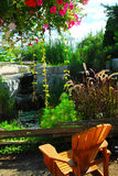 Patio and pond landscaping. Natural stone pond and patio landscaping with wooden chair Stock Photos