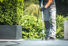 Patio Pressure Cleaning. Caucasian Men Washing His Concrete Floor Patio Using High Pressured Water Cleaner stock images
