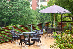 Patio rattan chairs and table in raining stock image