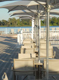 Patio Resort. Shot of some table, chairs, and umbrellas. Lake and vegetation as a background stock photo