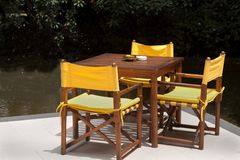 Patio table and chairs. Yellow wood table sitting on a patio next to a pond Stock Photo