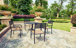Outdoor backyard patio in landscaping garden with furniture. Outdoor patio with furniture in landscaping garden. Backyard patio with table and chairs in sunshine royalty free stock photos