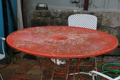 Patio table and chairs. The rusted orange patio table is very old Stock Image
