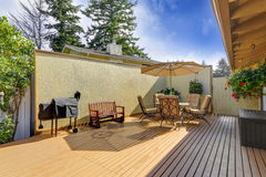 Patio table set with opened umbrella. Wooden walkout deck Stock Photo