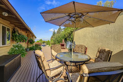 Patio table set with opened umbrella. Wooden walkout deck Stock Images