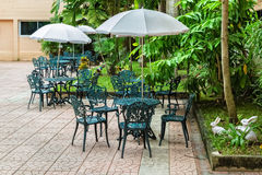 Patio with Tables and Alloy chairs. Under Umbrella in Garden Royalty Free Stock Photo