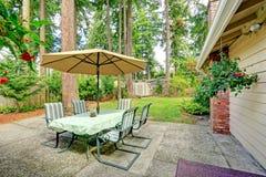 Patio trasero de la casa del campo con la tabla de patio Imagen de archivo libre de regalías