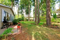 Patio trasero de la casa del campo con los árboles Fotografía de archivo