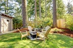 Patio trasero exterior casero con las sillas y los árboles de pino. Foto de archivo libre de regalías