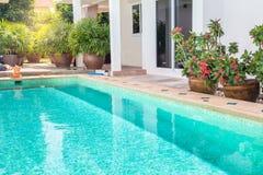 Patio trasero moderno de una piscina con la casa imagen de archivo