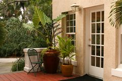 Patio in Tropics. With  plants in pots on red tiled floor, French doors, Bird of Paradise Stock Image