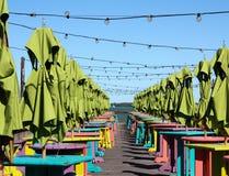 Patio vide de bord de l'eau avec les tables, les tabourets et le vert colorés um Photos stock