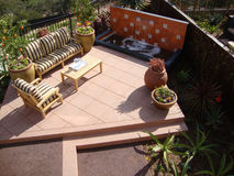 Patio with a water fountain. Patio with a couch and chair and a water feature. The landscape is drought tolerant with succulent plants Stock Image