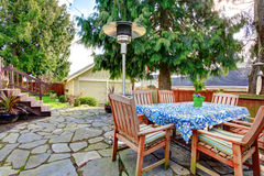 Patio with wood table set and heat lapm. Stoned patio area with wood dining table set, heat lamp Stock Images