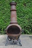 Patio woodburner. A rusty and weathered patio wood burner, known as a chimenea in the UK Royalty Free Stock Image